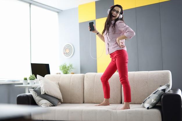 Mulher está de pé no sofá com fones de ouvido, rindo e segurando o smartphone nas mãos