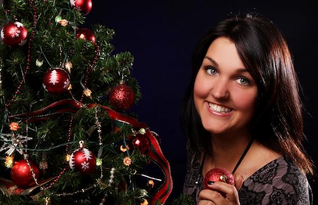 Mulher está decorando a árvore de natal