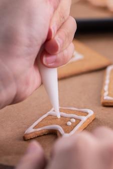 Mulher está decorando a casa de biscoitos de gengibre com cobertura de creme de confeiteiro branco glacê no fundo da mesa de madeira, papel manteiga na cozinha, close-up, macro.