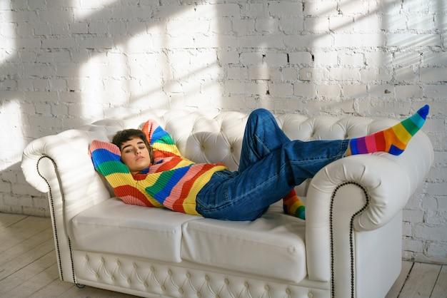 Mulher está deitada em um sofá com uma camisola multicolorida e meias