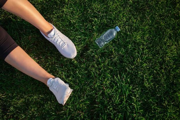 Mulher está deitada no gramado verde do parque. mulher feliz relaxando na grama durante o dia ensolarado de verão. pés femininos com tênis brancos. vista do topo. banner de grande formato