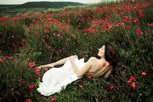 Mulher está deitada nua coberta uma camisa branca entre flores de papoula