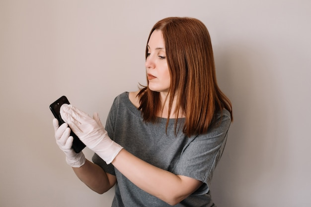 Mulher está desinfectando o celular. conceito de coronavírus