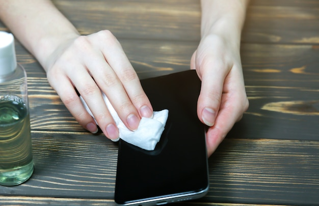 Mulher está desinfetando o smartphone com almofadas de algodão. anti-séptico durante a pandemia de coronavírus. perigo de vírus. dispositivos perigosos sujos. medidas de segurança.
