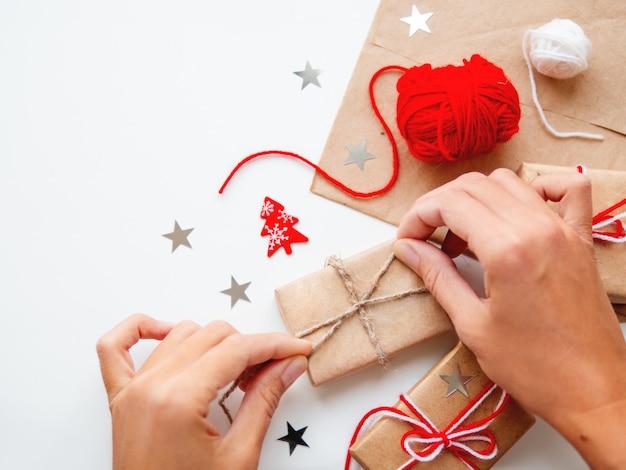 Mulher está embalando presentes de natal e ano novo diy em papel ofício. presentes amarrados com fios brancos e vermelhos.
