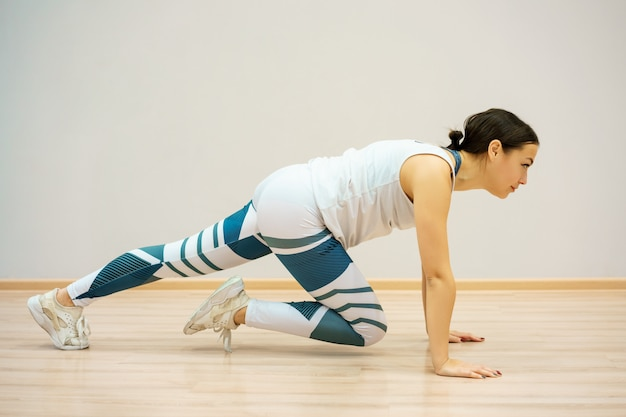 Mulher está envolvida em fitness em casa no tapete azul, em roupas esportivas. treino e alongamento em casa