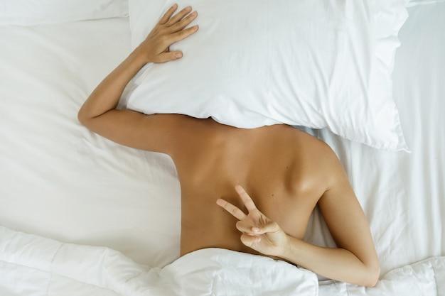 Mulher está escondida debaixo do travesseiro e não quer acordar
