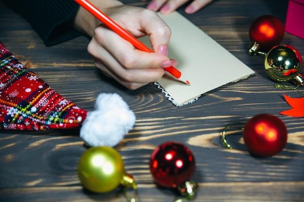 Mulher está escrevendo cartões postais de natal. saudações com feriados. feliz ano novo. parabéns aos amigos e familiares. decorações na mesa de madeira. clima aconchegante. copie o lugar do espaço.