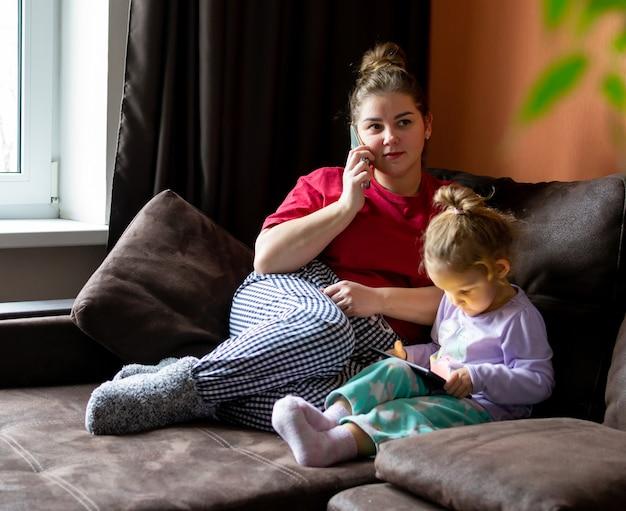 Mulher está falando com um telefone celular e uma garota jogando no tablet. mãe e filha ficam em casa, sentadas no sofá da sala.