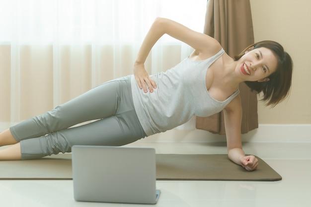 Mulher está fazendo exercícios de prancha lateral, olhando para o laptop na sala de estar no tapete em casa.