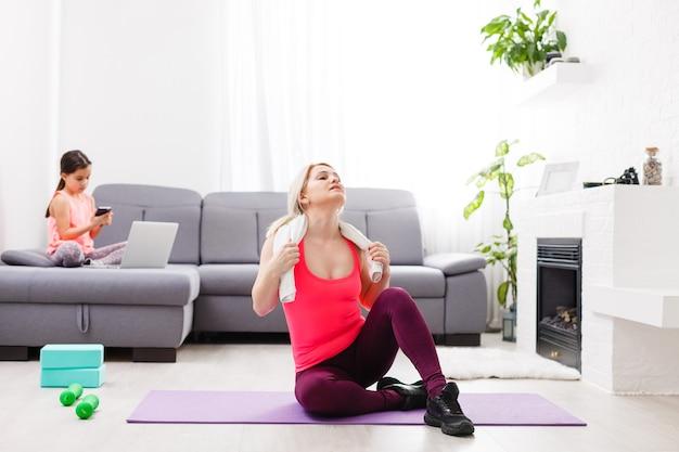 Mulher está fazendo ioga online com laptop durante o isolamento em sua sala de estar, nenhum treino com equipamento, dicas de meditação para iniciantes. tempo para a família com crianças, fique em casa.