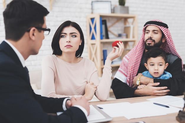 Mulher está fazendo perguntas sobre o divórcio, o homem está segurando o filho.