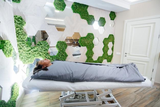 Mulher está fazendo um envoltório de corpo inteiro de procedimento de cosmetologia em um moderno salão de beleza.