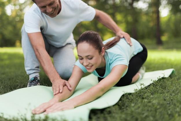 Mulher está fazendo warm-up em um tapete para yoga, um homem ajudando-a