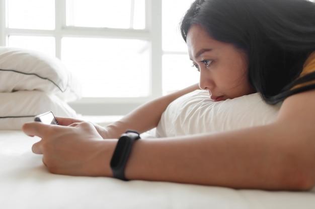 Mulher está jogando jogo para celular no quarto dela