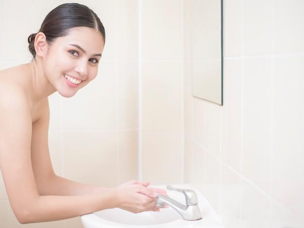 Mulher está lavando o rosto