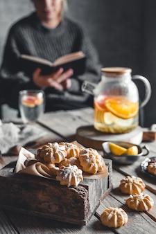 Mulher está lendo e chá quente com toranja fresca na mesa de madeira. bebida saudável, eco, vegana.