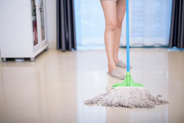 Mulher está limpando a casa com a esfregona