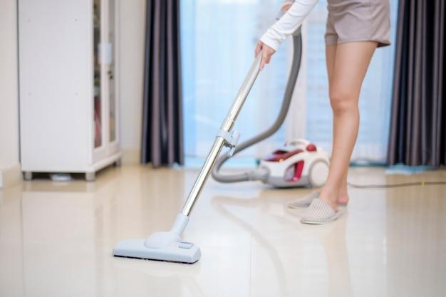 Mulher está limpando a casa com máquina de vácuo