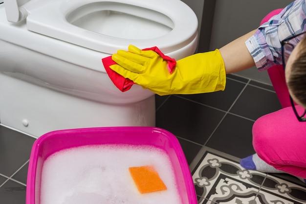 Mulher está limpando lave o banheiro