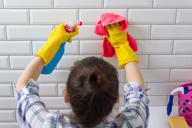 Mulher está limpando no banheiro em casa