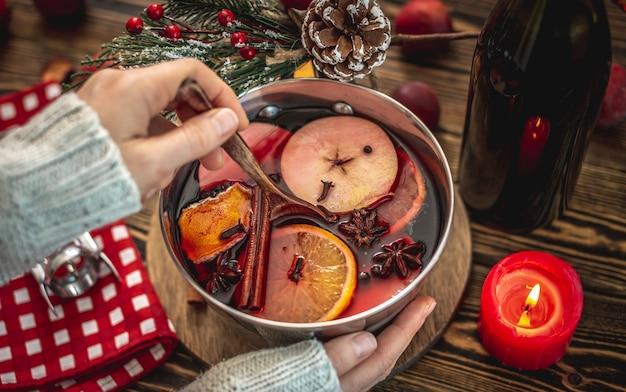 Mulher está mexendo vinho quente picante com especiarias em uma panela. conceito de atmosfera festiva acolhedora, clima de ano novo e natal.