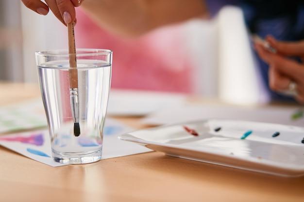 Mulher está molhando o pincel em um copo com água