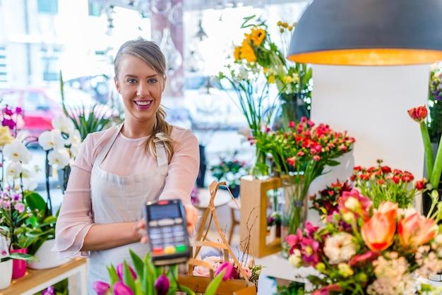 Mulher está oferecendo o terminal de pagamento para pagamento com cartão de crédito