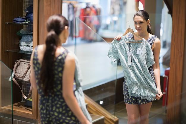 Mulher está olhando no espelho enquanto segura roupas