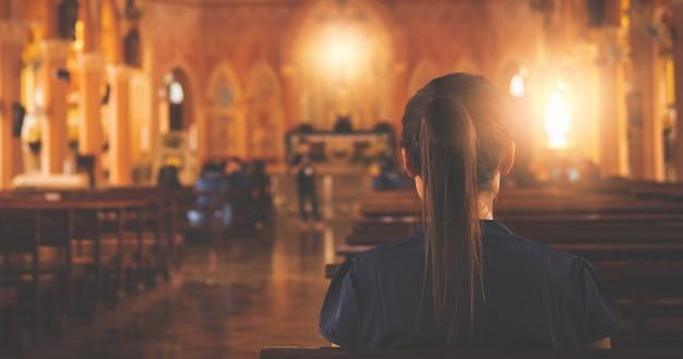 Mulher está orando a deus na igreja.