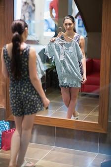 Mulher está parada na frente do espelho com roupas