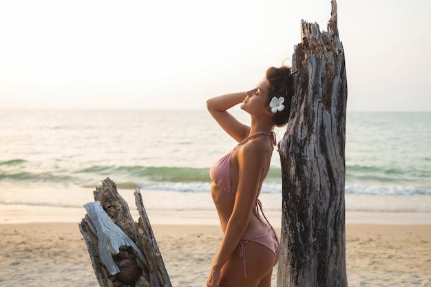 Mulher está posando ao lado da madeira na praia