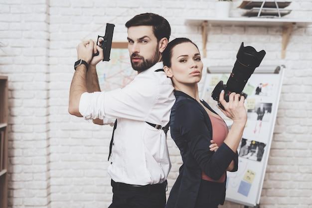 Mulher está posando com a câmera, o homem está posando com arma.