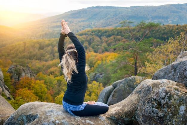 Mulher está praticando ioga e fazendo asana no topo da enorme pedra à noite