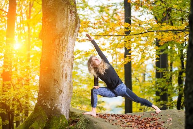 Mulher está praticando yoga na floresta de outono na grande pedra