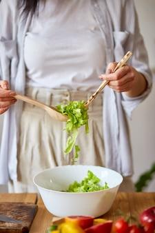 Mulher está preparando salada de legumes na cozinha, misturando folhas de salada e legumes em uma tigela branca, conceito de comida saudável, vegan ou dieta.