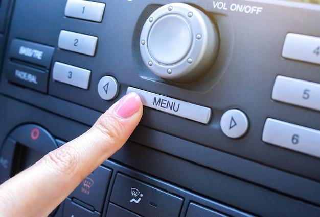 Mulher está pressionando o botão de menu no carro.