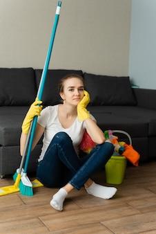 Mulher está pronta para limpar a casa. uma dona de casa está limpando a casa