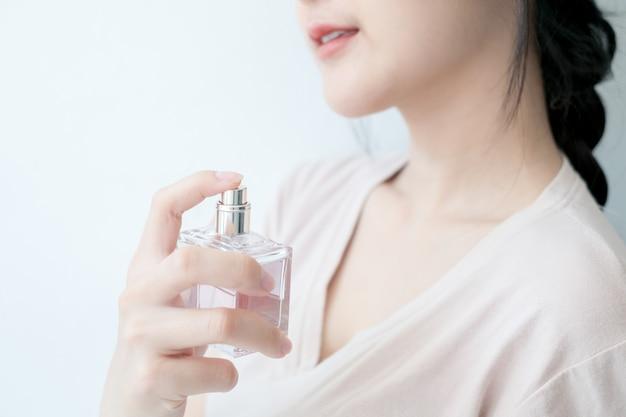 Mulher está pulverizando perfume no pescoço.