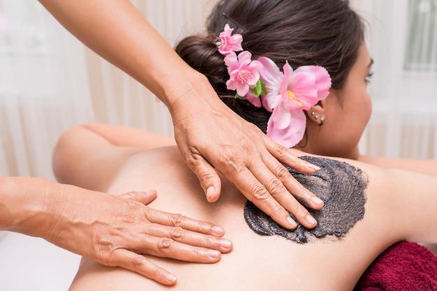 Mulher está recebendo esfoliação spa em branco nas costas