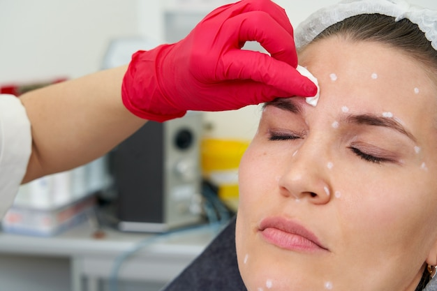 Mulher está recebendo injeções faciais rejuvenescedoras. a esteticista especialista está preenchendo as rugas femininas