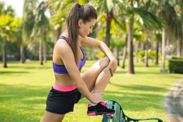 Mulher está se aquecendo antes de correr no parque