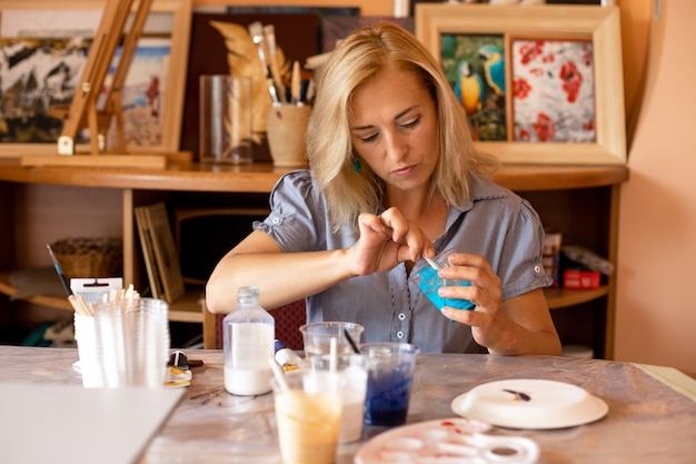 Mulher está se concentrando em mexer a tinta turquesa com a xícara e se preparando para o trabalho. trabalho em oficina criativa. pinturas de interiores. design e inspiração. trabalhe em casa. estilo de vida