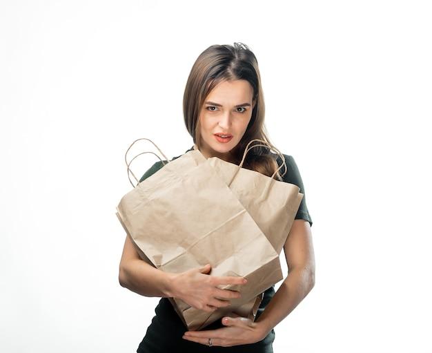 Mulher está segurando duas sacolas de compras de supermercado em fundo branco. sacos de papel marrom claro nas mãos. fundo isolado.