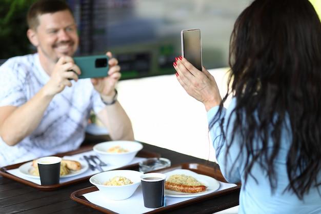 Mulher está segurando o smartphone nas mãos, o homem está filmando a revisão da novidade no smartphone no café.