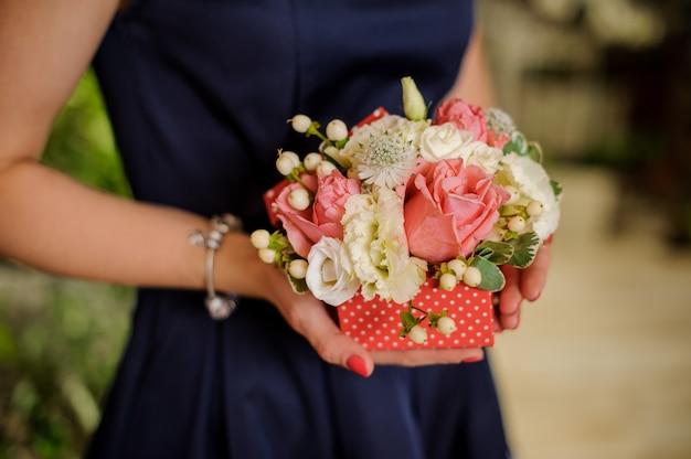 Mulher está segurando uma composição de flores concurso