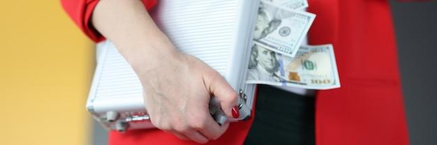 Mulher está segurando uma mala com muito dinheiro conceito de apostas e jogos de azar bem-sucedidos