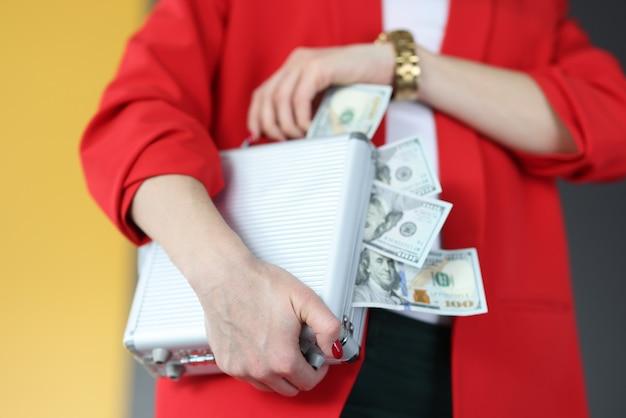 Mulher está segurando uma mala com muito dinheiro. conceito de jogo e apostas de sucesso