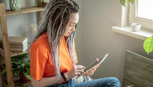 Mulher está sentada em uma cadeira em casa e usando um tablet para ler as notícias ou ver outras informações