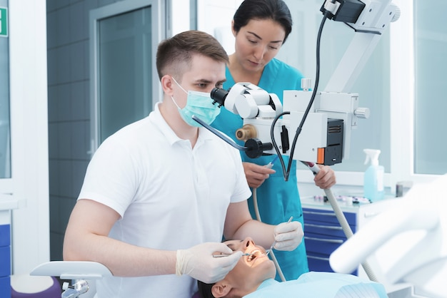 Mulher está sentada em uma cadeira odontológica na recepção de um dentista